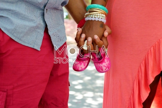 Closeup of Couple Holding Hands and Baby Shoes