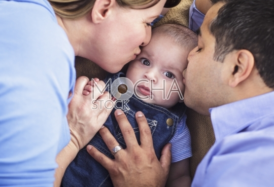 Mixed Race Parents Kissing Their Son