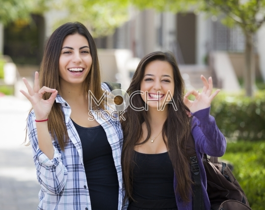 Mixed Race Female Students on School Campus With Okay Sign