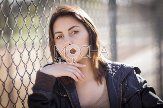Beautiful Young Woman Leaning Against Fence