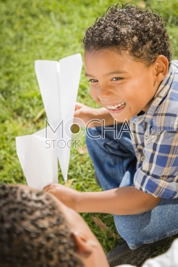 Smiling Mixed Race Father and Son Making Paper Airplanes