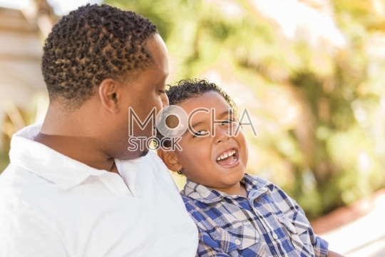 Happy Mixed Race Father and Son Talking Outdoors
