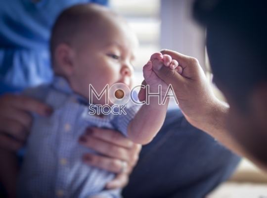 Cute Mixed Race Infant Boy Holds Father's Thumb