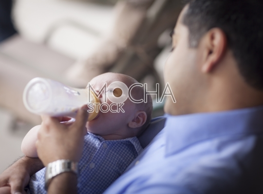Happy Hispanic Father Bottle Feeding His Mixed Race Son