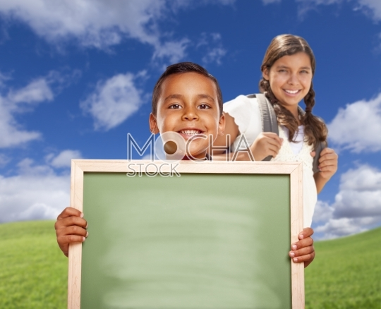 Hispanic Boy and Girl In Field Holding Blank Chalk Board
