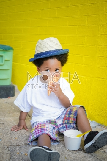 Cute Young Boy in Hat Eats Ice Cream Cone