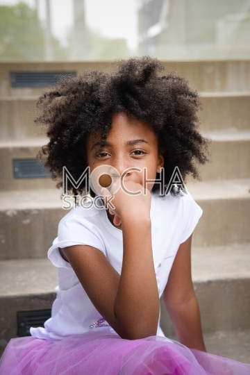 Young Girl with Afro Thinks as She Sits on Staircase