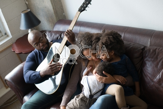 Children Lay on Mother While Father Serenades Them with Song