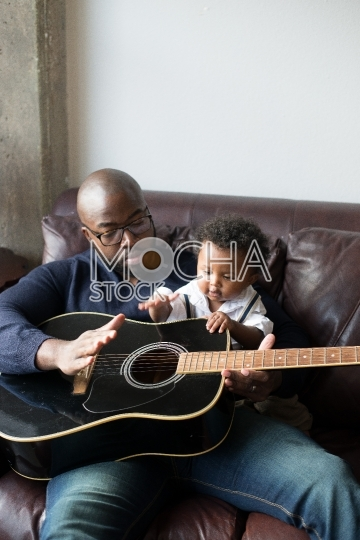 Father Teaches Young Son How to Play Guitar