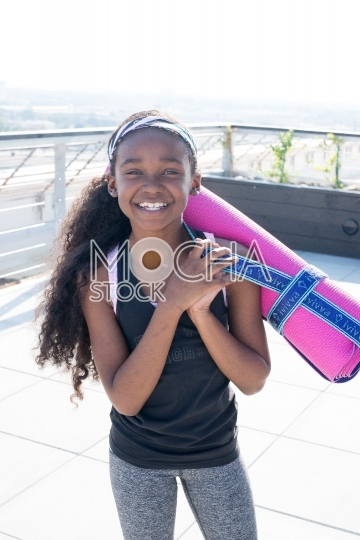 Young Girl with Yoga Mat Prepares for Class