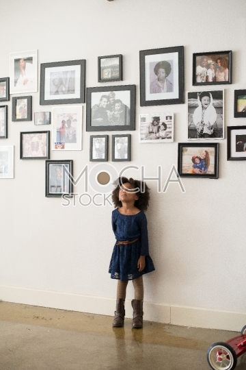 Beautiful Young Girl with Afro Looks Up at Pictures on Wall