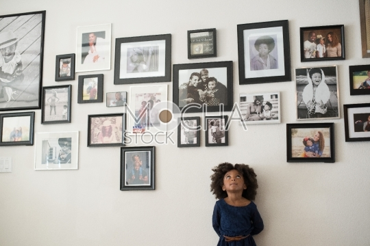 Young Girl Looks Up at Pictures on Wall