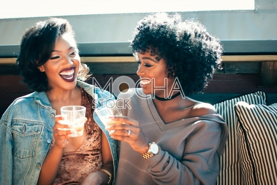 Two Friends Laughing While Drinking Cocktails