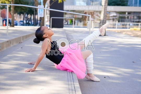 Adorable young ballerina wearing tutu and sitting on steps
