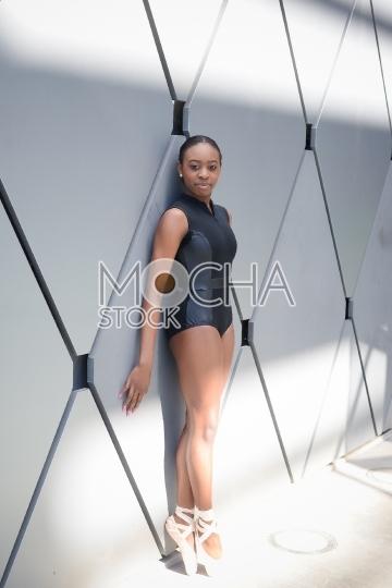 Young Ballet Dancer Stands En Pointe Near Wall