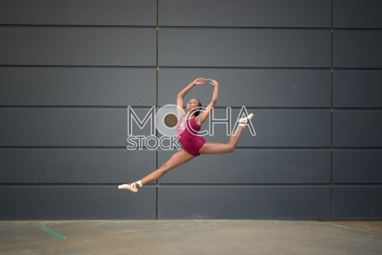 Girl wearing a leotard and ballet slippers and leaping