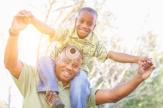 Happy African American Father and Son Riding Piggyback Outdoors
