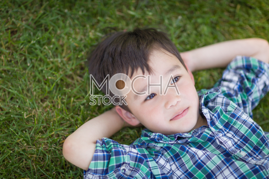 Thoughtful Mixed Race Chinese and Caucasian Young Boy Relaxing O