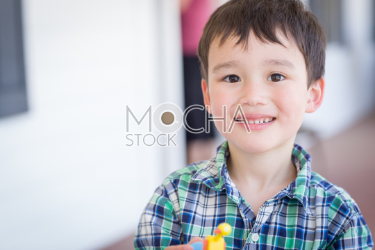Portrait of Mixed Race Chinese and Caucasian Young Boy With Toy