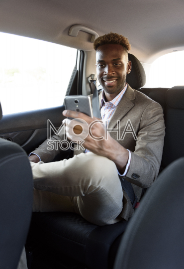 man sitting in back of car with phone