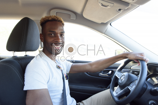 Smiling man with hand on steering wheel in car