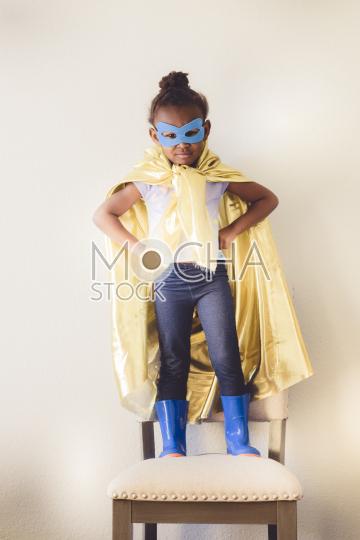 Little girl dressing up as superhero
