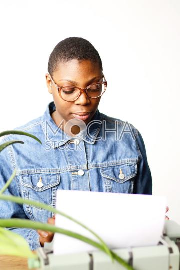 Woman wearing glasses uses typewriter
