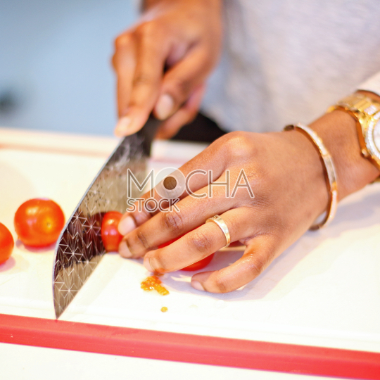 Female hand cutting cherry tomatoes