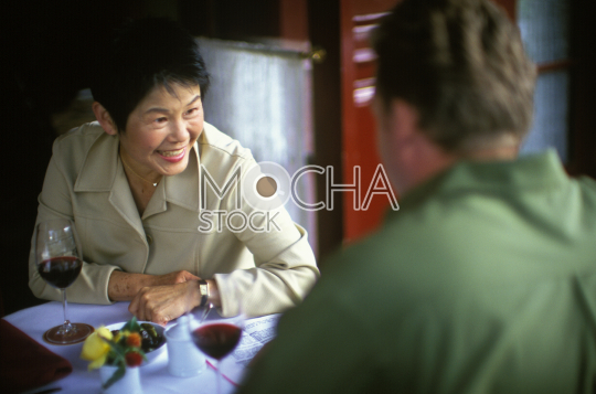 Smiling mid adult woman dining with a male friend at a restaurant