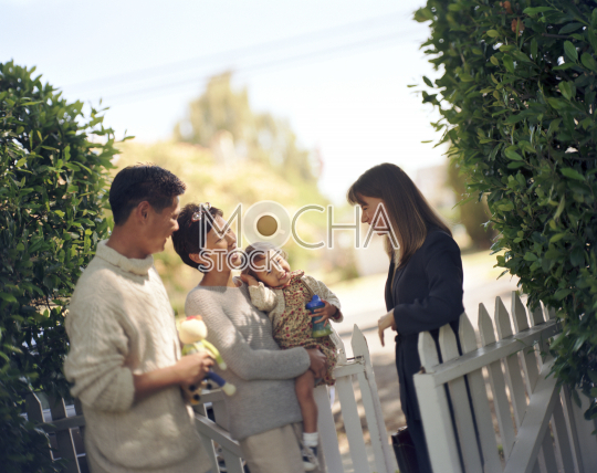 Couple with daughter talking with woman in backyard