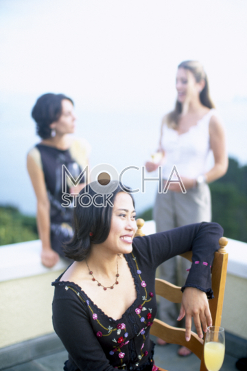 Smiling mid-adult woman sitting on a balcony during a social gathering