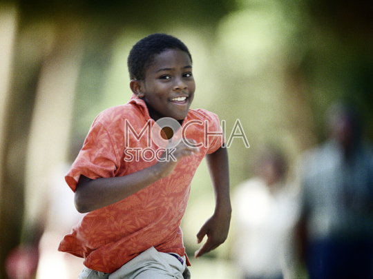 Front view a young boy running and smiling