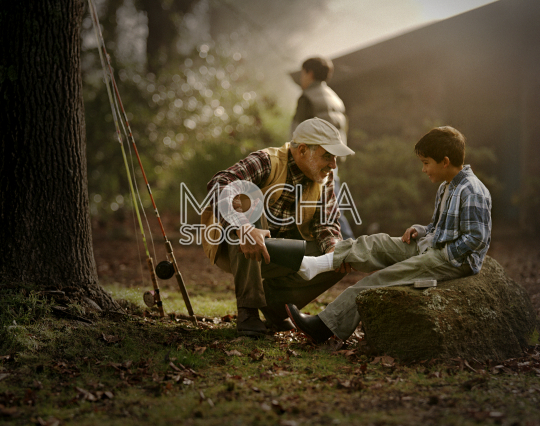 Smiling grandfather helping his grandson put on a rubber boot while out fishing in the country