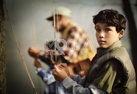 Portrait of a boy holding a fishing rod while out fishing with his grandfather and brother