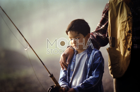 Young boy with his grandfather's arm around him while standing holding a fishing rod