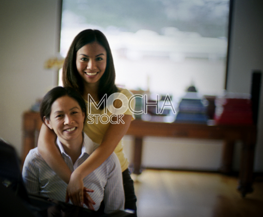 Portrait of a smiling mid-adult woman and her daughter