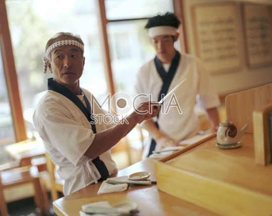Two Japanese chefs preparing for diners in a traditional restaurant