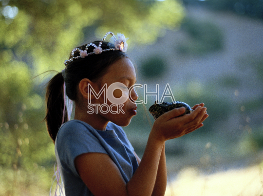 Young girl wearing a princess crown puckering up to kiss a green frog