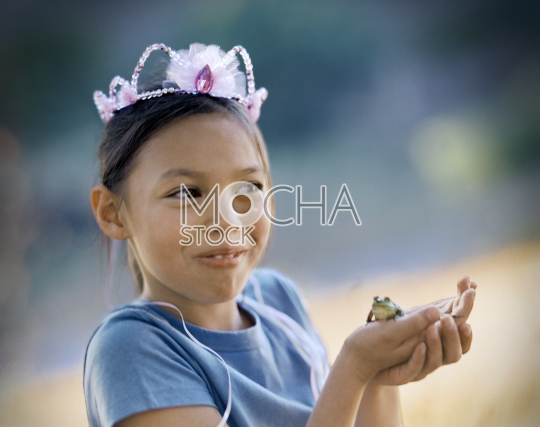 Young girl wearing a crown and holding a green frog in her hands