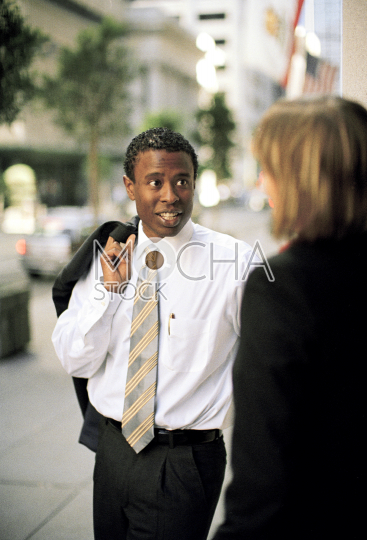 Businessman and woman talking in the street