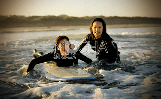 Two women surfers with surfboard