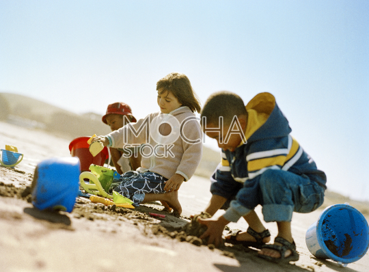 Three young kids building sandcastles at the beach