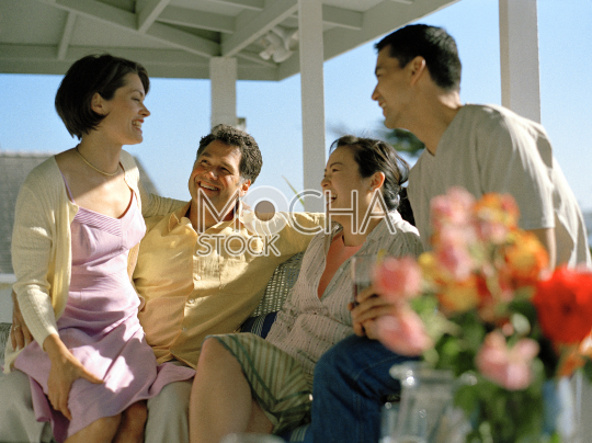 Two couples sitting on a verandah