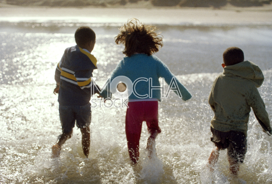 Rear view of three children running through shallow water at the beach