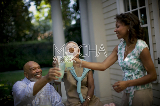 Mature couple sharing a toast with their daughter