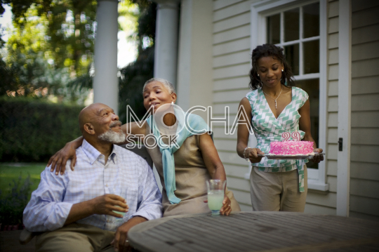 Mature couple celebrating their wedding anniversary with their daughter