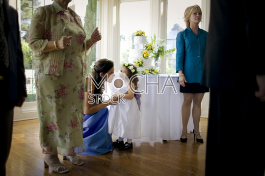 Bridesmaid comforting a young girl during a wedding reception