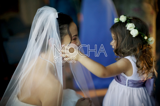 Young bride talking to flower girl at wedding