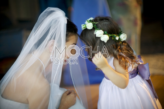 Young bride playing with  flower girl at wedding