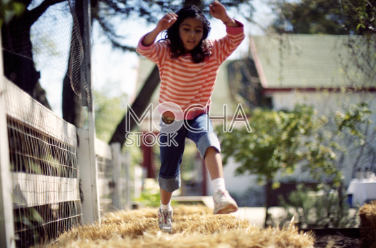 Young girl running and jumping along a grassy sidewalk